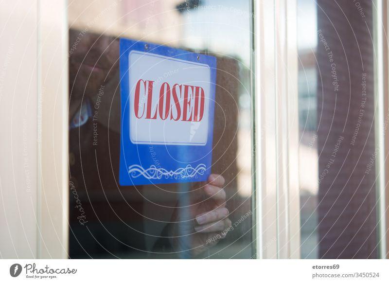 Geschäftsmann hängt geschlossenes Schild für Coronavirus covid-19 Vollbart Vorsicht zugeklappt Krise Tür Mitarbeiter Unternehmer Seuche Glas erhängen Mann