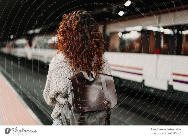 junge, schöne Frau am Bahnhof mit dem Handy, bevor sie den Zug erreicht. Ansicht von hinten. Reise-, Technologie- und Lifestyle-Konzept reisen Station bewegend