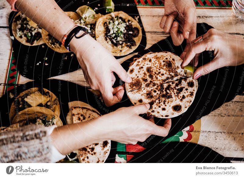 nicht erkennbare Gruppe von Freunden, die in einem Restaurant mexikanisches Essen essen. Köstliche Fajitas. Lebensstil im Freien Menschengruppe Lebensmittel