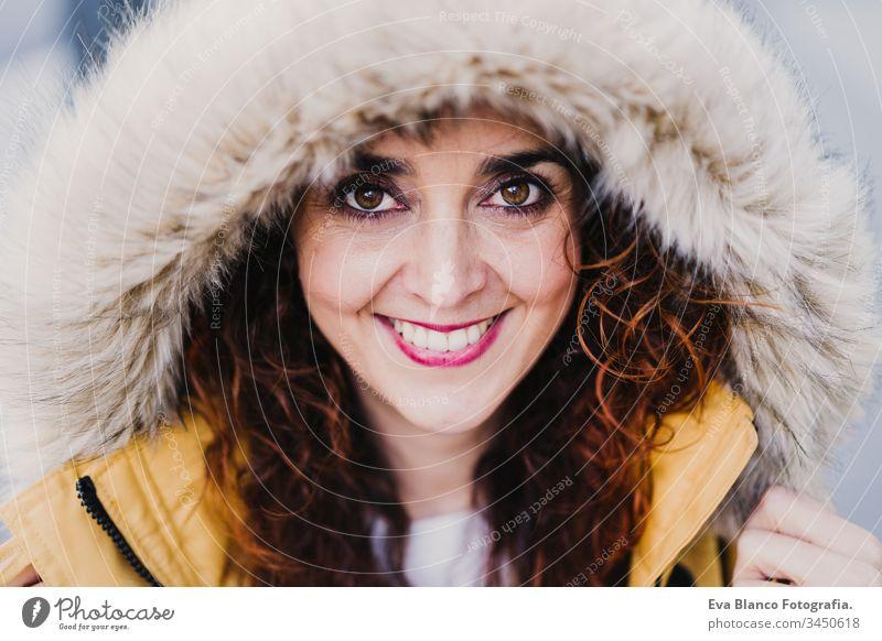 Porträt einer jungen schönen Frau mit Kapuze, die im Freien lächelt. Fröhlichkeit und Lebensstil Lächeln gelb Mantel Großstadt urban Straße Glück Kaukasier