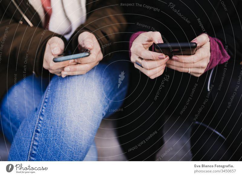 zwei nicht wiedererkennbare Freunde, die draußen auf der Straße mit dem Handy telefonieren. lifestyle- und reisekonzept Menschengruppe Freundschaft Tourist