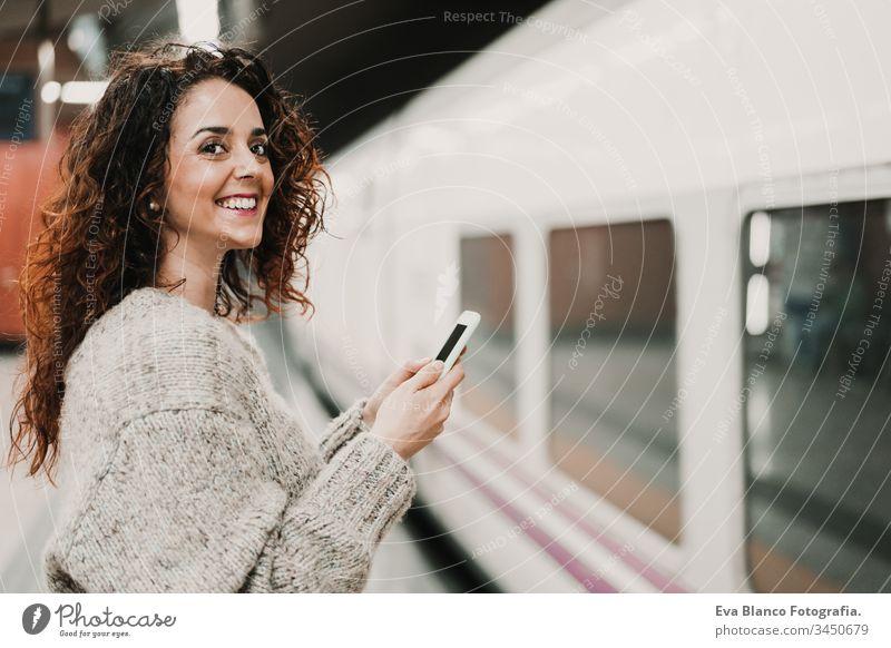 junge, schöne Frau am Bahnhof mit dem Handy, bevor sie den Zug erreicht. Reise-, Technologie- und Lifestyle-Konzept reisen Station bewegend Kaukasier Madrid