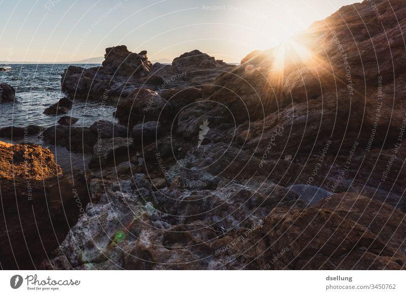 Felsige Küste bei Sonnenuntergang Felsenküste Stein Himmel Umwelt Tourismus Wasser Menschenleer Sommer natürlich Bucht Tag Horizont Licht Mittelmeer orange