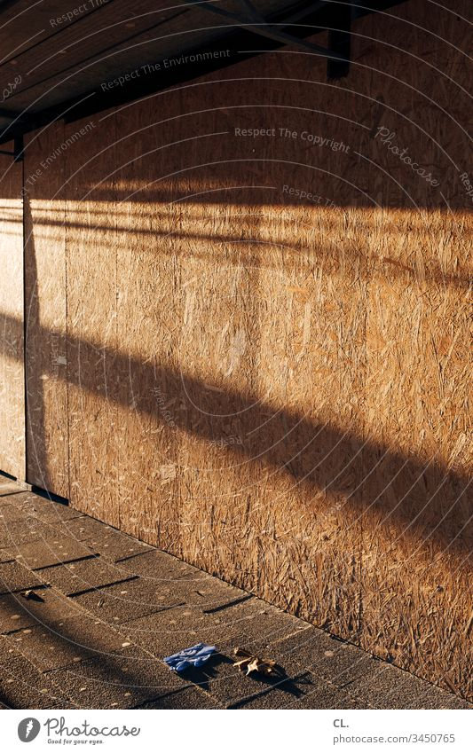 schutzhandschuh liegt auf dem gehweg Handschuhe Schutzhandschuhe Sonnenlicht Baustelle verlassen Wege & Pfade Verkehrswege trist Außenaufnahme Tag Menschenleer