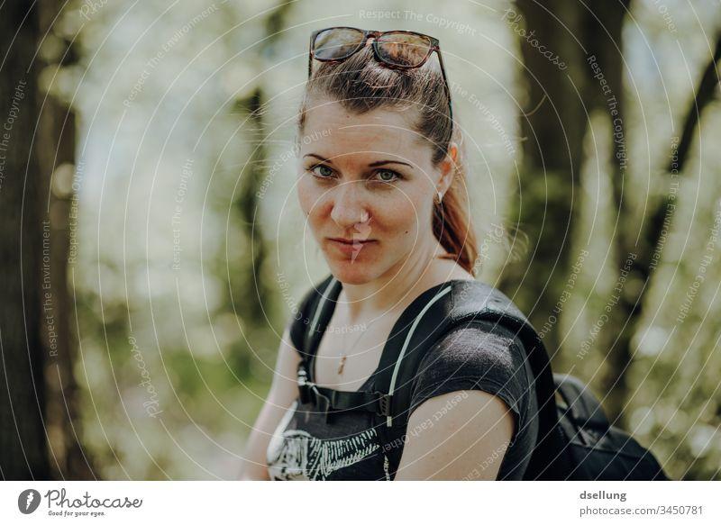 Junge Frau bei Wanderung im Wald mit Blick in die Kamera. Also natürlich geht sich nicht mit dem Blick in die Kamera wandern, sondern mit ihrem Mann, der sie dabei fotografiert, wie sie in die Kamera blickt.