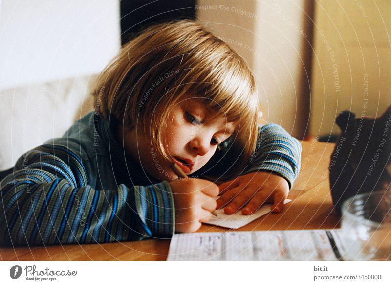 Kleines Mädchen sitzt zuhause am Tisch in der Sonne und malt und lernt schreiben für die Schule. Wohnung Bleibt daheim Bleibt zuhause drinnen Stimmung Gefühle