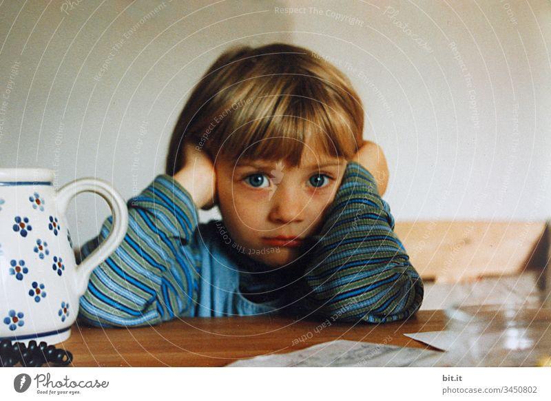 Kleines Mädchen sitzt ernst zuhause am Tisch, stützt den Kopf in die Hände und schaut etwas traurig..... Kleinkind Leben Mensch Kindheit daheim Erziehung