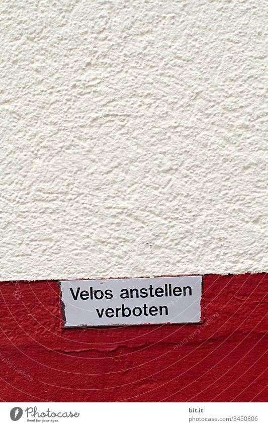 Schild an einer rot, weissen Hauswand aus Stein, in der Schweiz, mit Text: Velos anstellen verboten, als Hinweis auf Parkverbot für Fahrräder an der Mauer, in der Stadt.