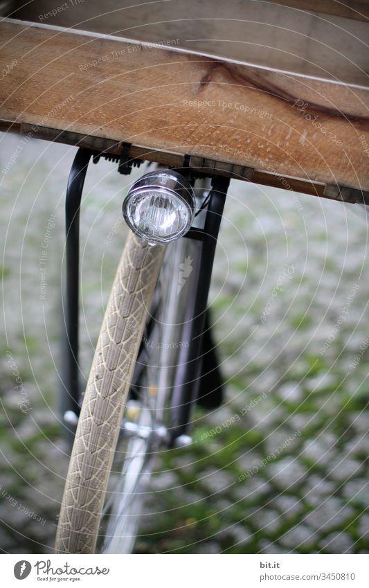 Lampe über dem Vorderrad eines Fahrrades mit Kiste aus Holz zum Transportieren, Einkaufen, auf Kopfsteinpflaster. Rad fahren Fahrradfahren Wege & Pfade Bewegung