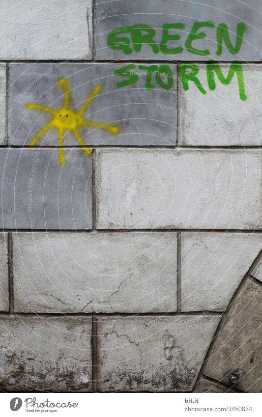 Green Storm mit Sonne als Schriftzug und Icon auf eine graue Mauer mit Mauersteinen gesprayt. Klimawandel green Greenstorm Sturm grün Wand Fassade Graffiti