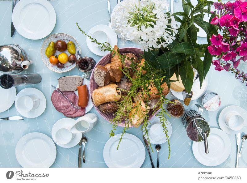 Frühstückstisch decken Tisch Geschirr weiß Blumen Wurstwaren rollen Tomaten bedeckt Farbfoto Lebensmittel Teller Innenaufnahme Backwaren Appetit & Hunger
