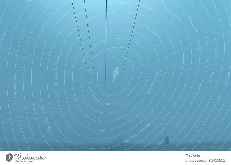 Mann im Nebel mann nebel nebelwand dunkel dunkelheit graublau alleine weg stille ruhig bedrückend landschaft ausserhalb draussen textfreiraum stromleitung