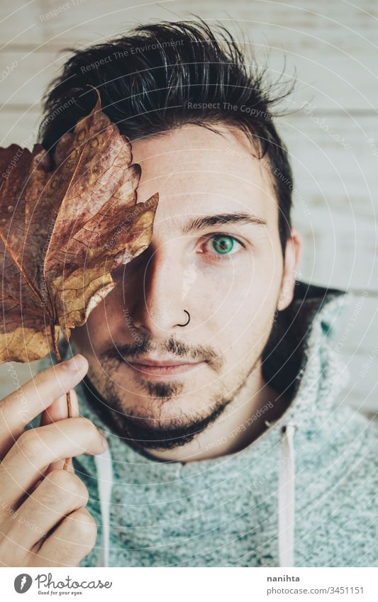 Junger Mann bedeckt sein Gesicht mit einem trockenen Blatt attraktiv cool männlich Porträt Herbst kreativ künstlerisch Vollbart Piercing Nase schließen