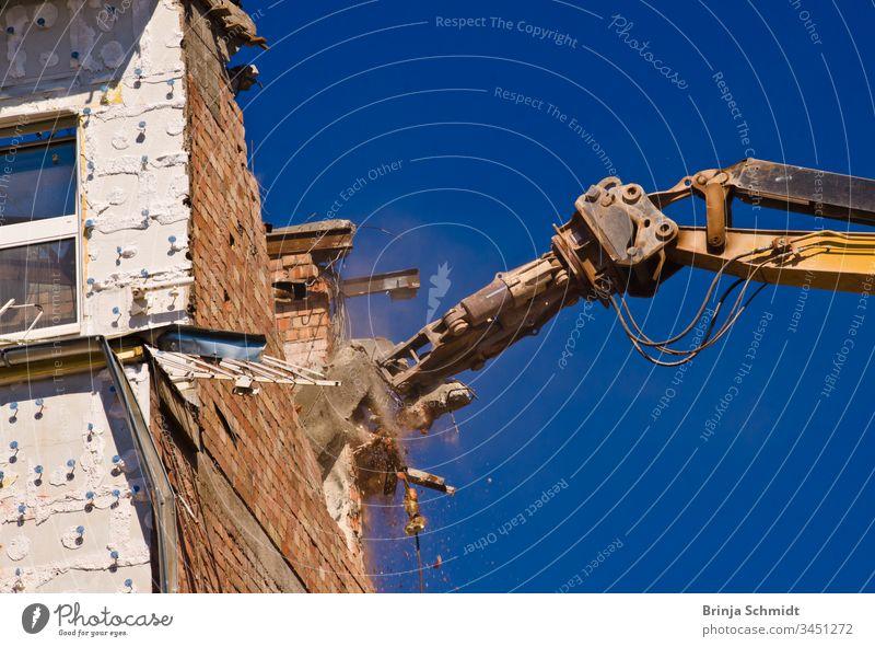 Abbruch eines Gebäudes mit einem Kran vor blauem Himmel Beruf Großstadt Bauherren alt Haus abbrechend erdrücken Außenseite Architektur Müll Business staubig