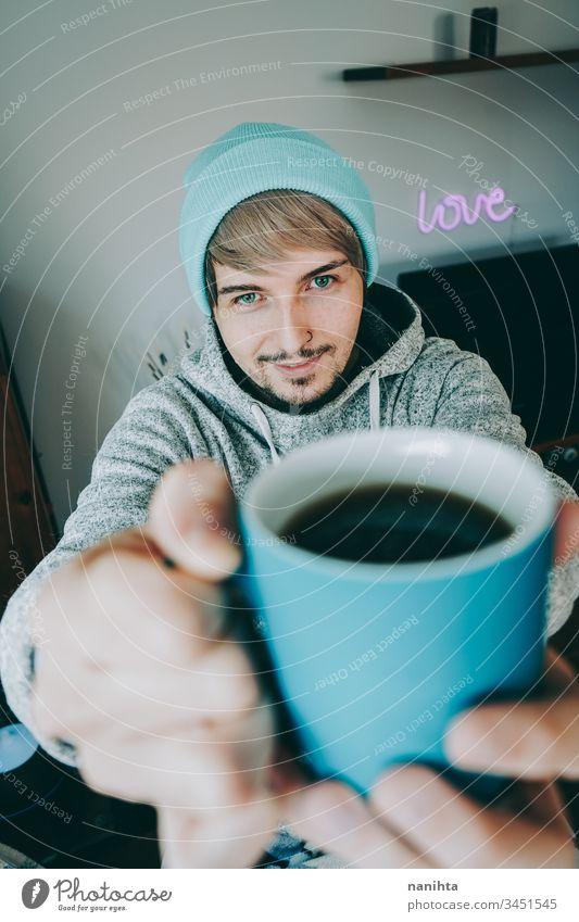 Junger Mann genießt eine Tasse Kaffee zu Hause männlich gemütlich heimwärts vereinzelt Quarantäne blau attraktiv gutaussehend Typ lässig anhaben Pyjama Tee