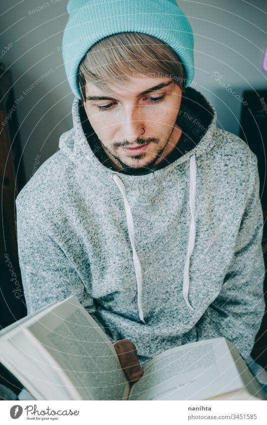 Junger Mann liest ein Buch in seinem Haus lesen heimwärts attraktiv Quarantäne Hobby Freizeit sich[Akk] entspannen genießend lernen Schüler jung Jugend