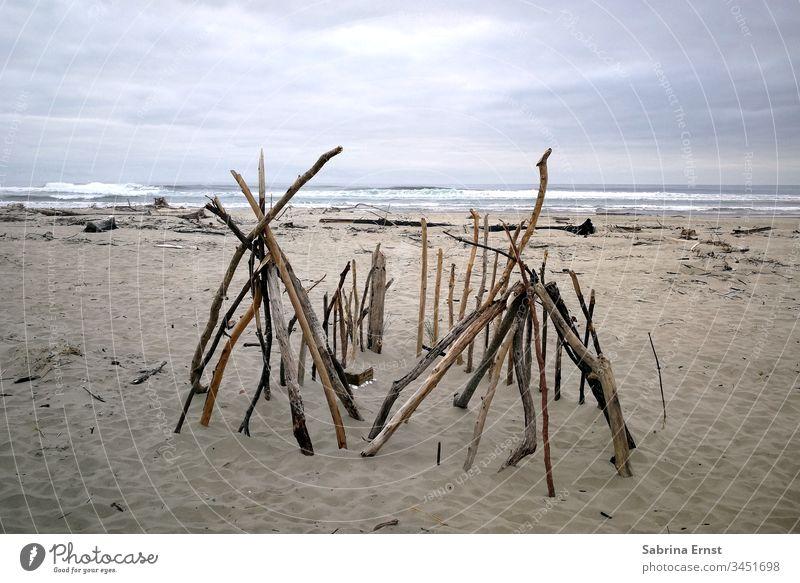 Holzzelt an einem Strand in Oregon hölzern Zelt Sand Meer Wasser grau raues Wetter reisen schön Urlaub Wellen Stöcke selbst gemacht Haus Hütte wood wooden