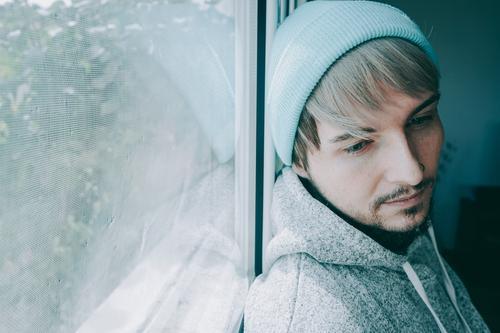 Junger Mann allein zu Hause in der Nähe eines Fensters männlich Porträt vereinzelt heimwärts gesperrt Quarantäne einsam Selbst attraktiv gutaussehend Typ lässig