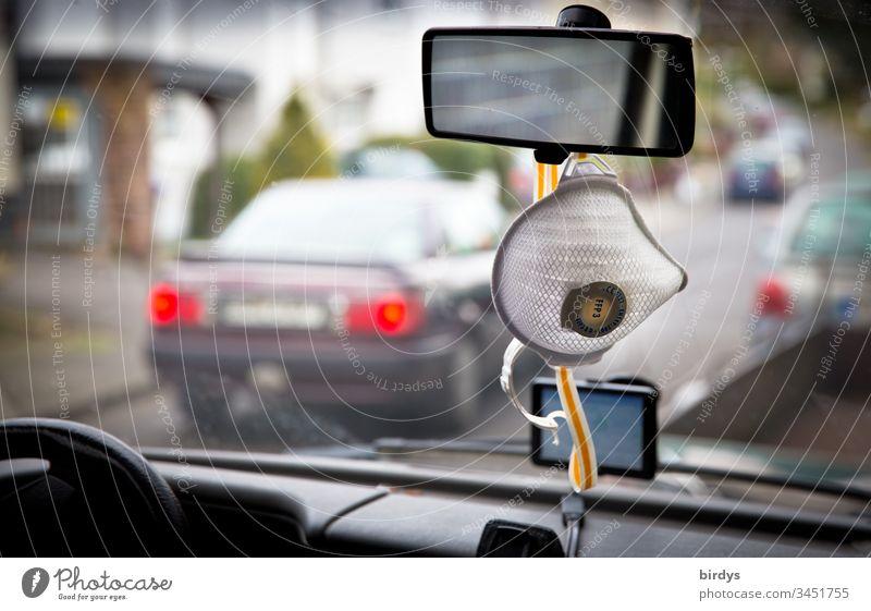 Atemschutzmaske der Schutzklasse FFP3 hängt griffbereit am Rückspiegel eines Autos, Mundschutz. CE-zertifiziert Pandemie Infektion Coronavirus Corona-Virus