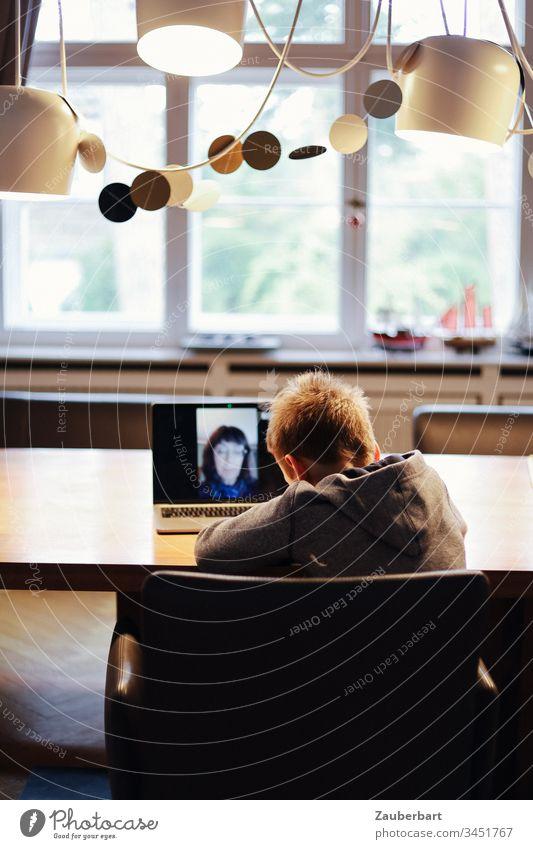 Kleiner Junge, Schulkind zuhause, im Video-Chat mit seiner Lehrerin, am Esstisch vor Fenster Kind Notebook Tisch homeschooling stay at home stayhome Grundschule