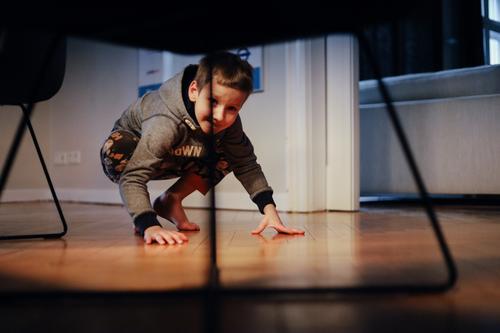 Junge beim Spielen in der Hocke schaut unter einen Tisch mit modernen Stühlen Kind Kindheit schauen suche verstecken Wohnung Wohnzimmer Innenaufnahme