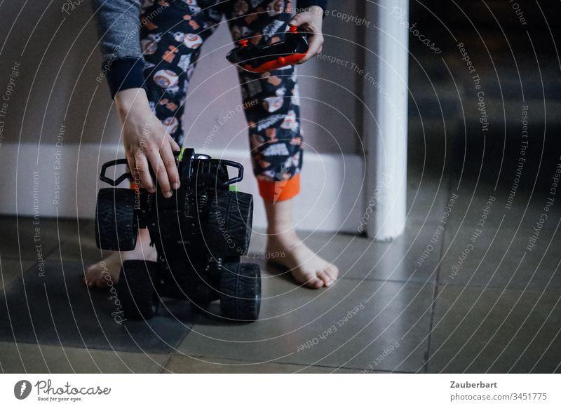 Kind spielt zuhause mit Fernsteuerauto im Schlafanzug Kindheit spielen Füße Spielzeugauto Fliesen bunt Spaß Freude Farbfoto Freizeit & Hobby niedlich Junge