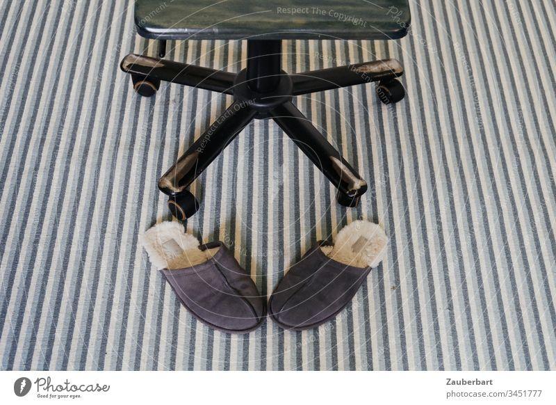 Schreibtischstuhl auf gestreiftem Teppich freut sich über das Homeoffice, davor Puschen Hausschuhe Streifen grün Innenaufnahme Detailaufnahme Farbfoto