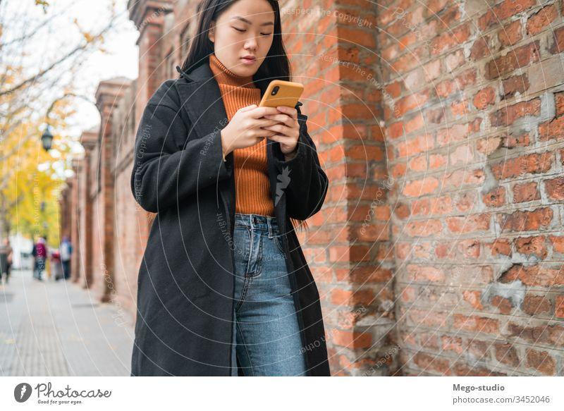 Asiatische Frau, die ihr Mobiltelefon benutzt. Straße Smartphone Telefon asiatisch Mobile Menschen urban klug Funktelefon Text jung SMS Nachricht im Freien