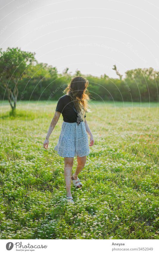 Eine junge Frau geht auf einem Feld mit kleinen Blumen 2017-2020 erste Einfuhr Junge Frau Mädchen elegant Freigeist Jugendliche Mensch feminin Stil schön