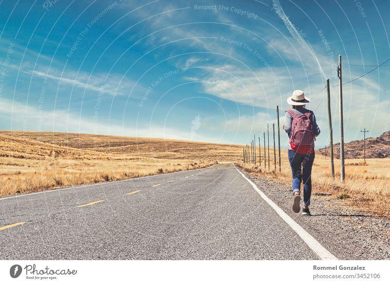 Schöne Frau trampt auf der Straße im Wald, trampen mit Daumen nach oben auf einer Landstraße, Konzept des Reisens und Trampens. im Freien Koffer laufen
