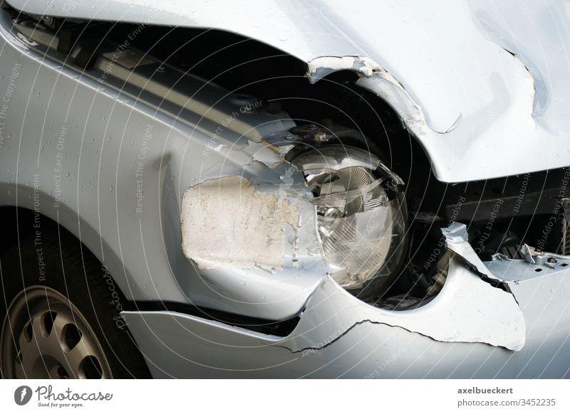 Autowrack nach einem Unfall mit Blechschaden PKW zerstört Scheinwerfer Motorhaube Beule Kollision Schaden Reparatur Verkehr Metall Automobil Versicherung
