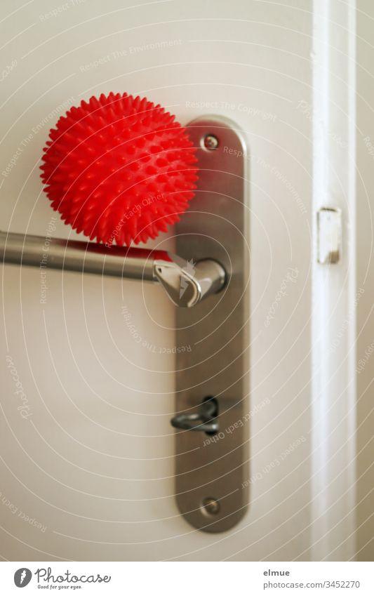 roter Ball als Sinnbild für Corona-Virus liegt auf einer Türklinke Coronavirus Covid-19 Infektion Ansteckungsgefahr Schmierinfektion Übertragung Symbol Grippe