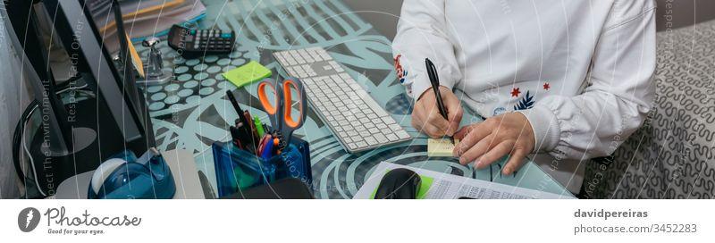 Frau, die von zu Hause aus mit dem Computer arbeitet Heimarbeitsplatz Coronavirus Quarantäne Einsperrung Notiz schreiben Transparente Netz Kopfball Panorama