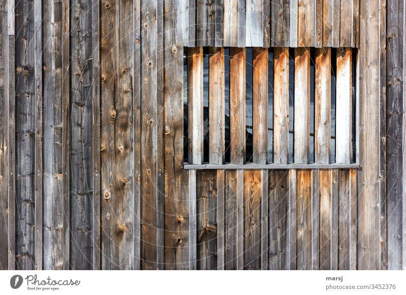 Holzwand mit einem Fenster, das mit Kanthölzern verbarrikadiert ist. braun Holzmaserung Wand Rechteck rechteckig geometrisch verwittert raue Kanten
