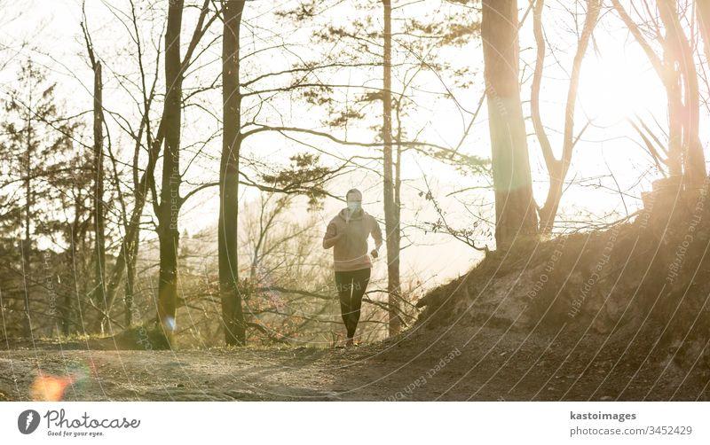 Das Corona-Virus, oder Covid-19, verbreitet sich auf der ganzen Welt. Porträt einer kaukasischen, sportlichen Frau, die beim Laufen in der Natur eine medizinische Schutzmaske trägt.