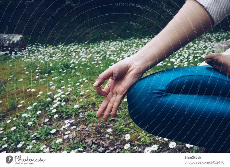 Junge Frau sitzt in Lotus-Pose, im Frühling mit Gänseblümchen im Freien Yoga Lotos jung Natur Meditation Margeriten Gesundheit Hintergrund Übung grün Gräser