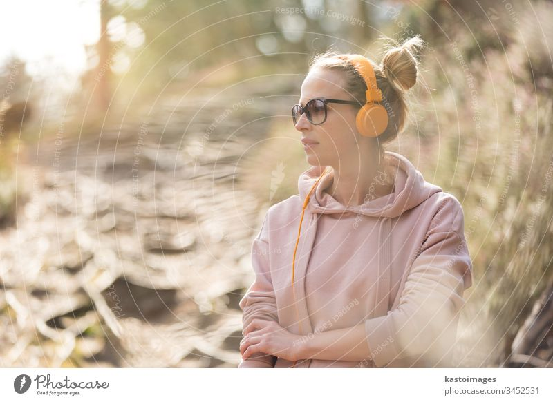 Porträt einer schönen Sportlerin mit Sonnenbrille, Kapuzenpulli und Kopfhörer beim Training im Freien Frau Mädchen Natur aktiv Läufer Sportbekleidung jung
