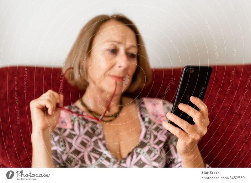 Elegante, reife Frau, die ein Smartphone benutzt, während sie auf dem Sofa sitzt virtuell einkaufen Lifestyle-Elektronik Gespräch Halt hübsch Talkrunde
