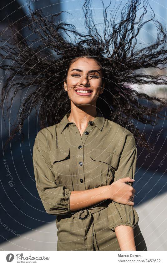 Junge attraktive Frau mit ihrem gewellten Haar im Wind lächelnd Lächeln Porträt heiter junger Erwachsener Vorderansicht Spaß Behaarung in die Kamera schauen