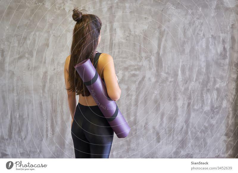Frau in einem Yogastudio im Haus, die eine Matte hält. Atelier jung Übung Fitness Pose schön Training Körper Person Gesundheit Meditation Hintergrund