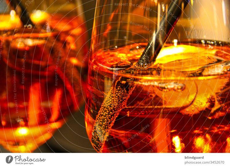 Schwarzer Strohhalm und Eiswürfel in glänzendem Cocktailglas mit oranger, alkoholhaltiger Flüssigkeit mit Luftblasen, die als Aperitif gereicht wird und mit einer Zitronenscheibe garniert serviert wird. Und Wer sich solche Titel ausdenkt macht mir Angst.
