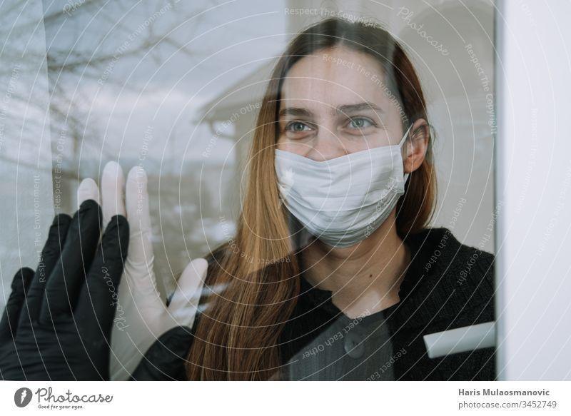 glückliche Frau, die sie gebraten sah und die sie wegen eines Coronavirus covid-19 mit Maske und Handschuhen am Fenster zu Hause besuchte soziale Distanzierung