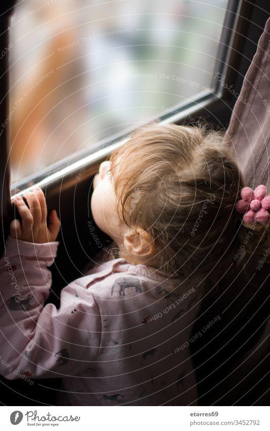 kleines Mädchen, das aus dem Fenster schaut Baby blond Kaukasier Konzept Coronavirus covid.19 Grippe heimwärts Haus Kind wenig Blick Aus im Freien Person