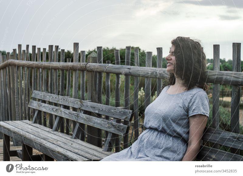 junge hübsche brünette Frau mit lockigen Haaren sitzt auf einer Holzbank vor einem Bretterzaun in den Dünen in Strandnähe und genießt den Urlaub lockige Haare