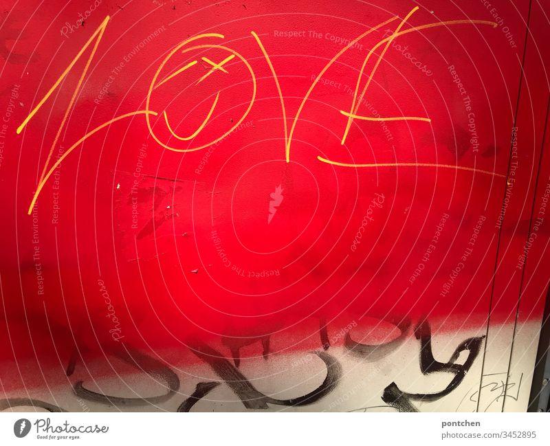 Graffiti gelbe Schrift auf rotem Untergrund englisches Wort love, smiley und schwarzes Geschmiere Smiley subkultur geschmiere jugendkultur illegal verboten