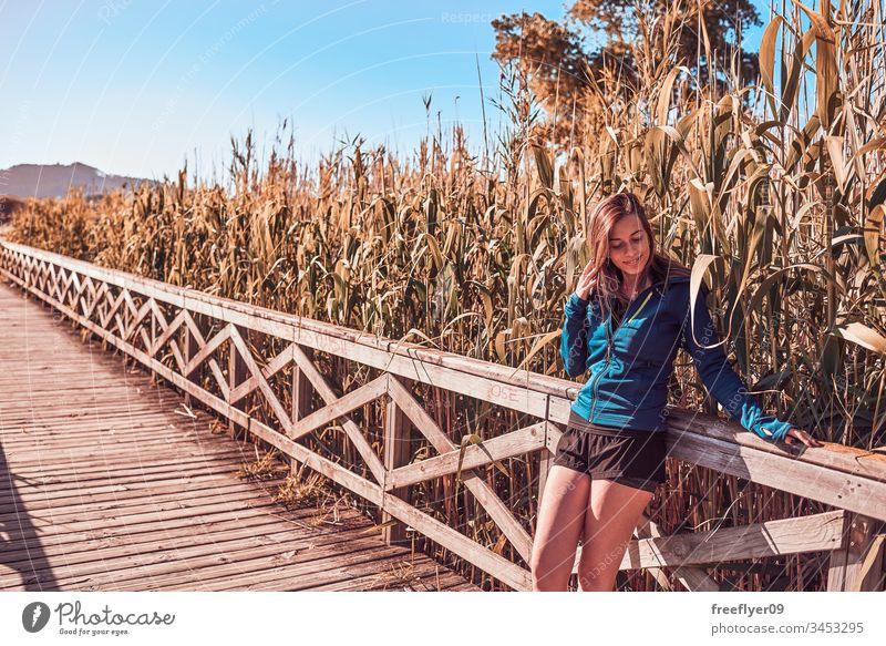 Junge Frau geht an einem Holzsteg entlang Playa Amerika Abenteuer Körper Brücke Steg Wald Freiheit Mädchen Gesundheit Landschaft landschaftlich gestaltet