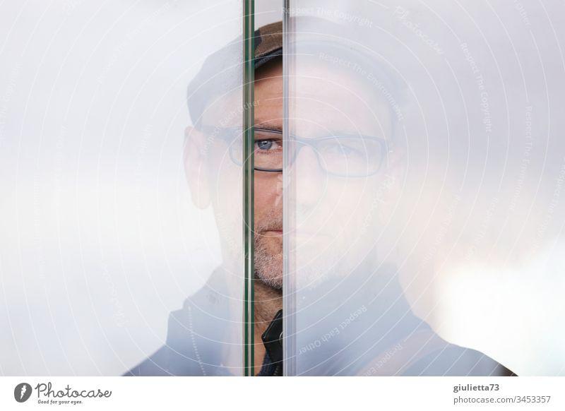 Mann der hinter einer Glaswand steht und mich durch einen Spalt beobachtet Senior 1 Mensch 45-60 Jahre 60 und älter Brille grauhaarig Blick authentisch ruhig