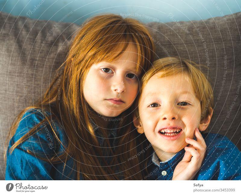 Zwei blonde kleine Kinder in blauen Hemden auf dem Sofa Lächeln Gesicht Umarmung Familie Liebe Geschwister Bruder Schwester Rotschopf wenig lustig süß Angebot