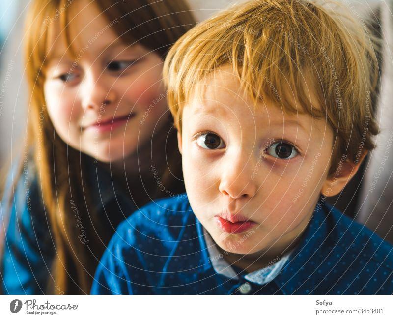 Zwei blonde, süße Kinder in blauen Hemden Lächeln Gesicht Familie Geschwister Bruder Schwester Rotschopf wenig lustig Angebot Zusammensein nah im Innenbereich