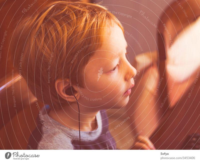 Süßer kleiner Junge spielt mit Kopfhörer am Computer Kind Technik & Technologie spielen Internet Freizeit männlich Person jung Lifestyle wenig Musik modern